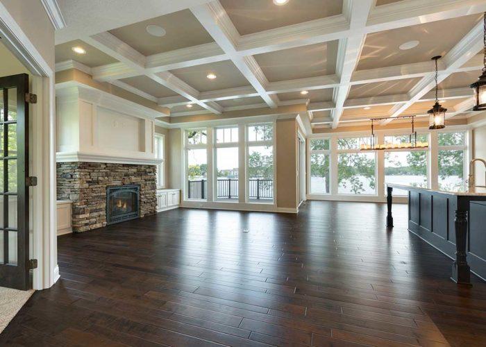 Dark wood flooring in great room with exposed beam ceiling