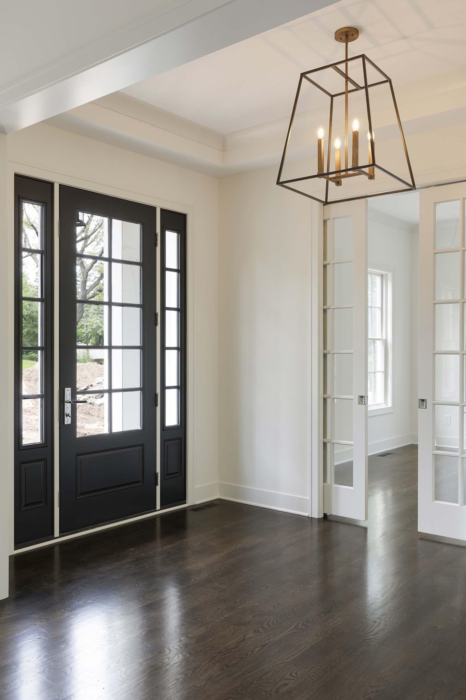 Colonial On The Creek Foyer Black Door and Designer Lighting