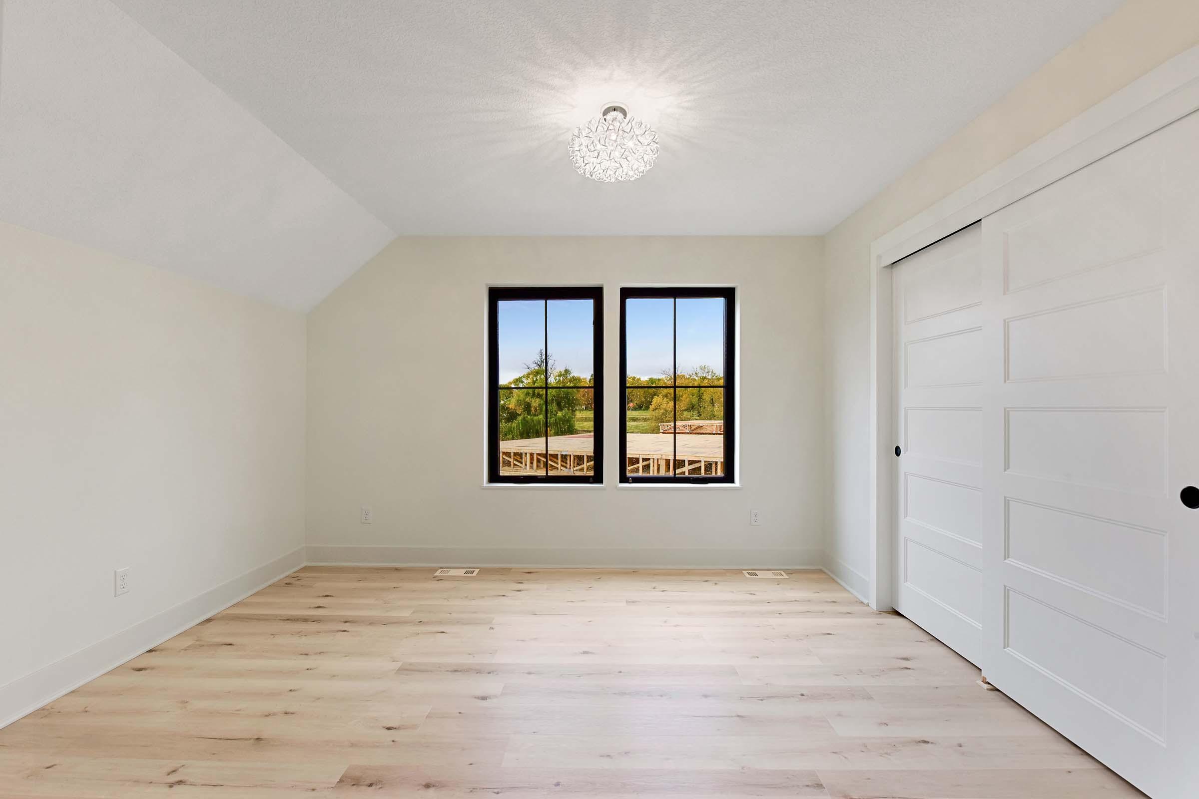 bonus room with two windows and wood flooring above garage